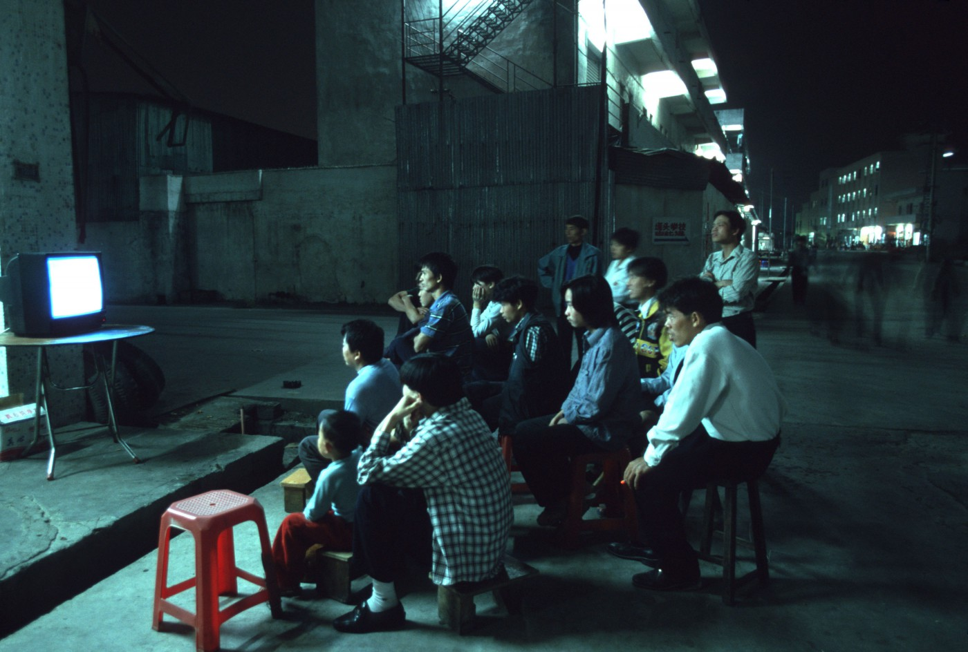 Greg Girard, </span><span><em>Factory Workers Watching TV, Shenzhen, 2000</em>, </span><span>30 x 40 inches