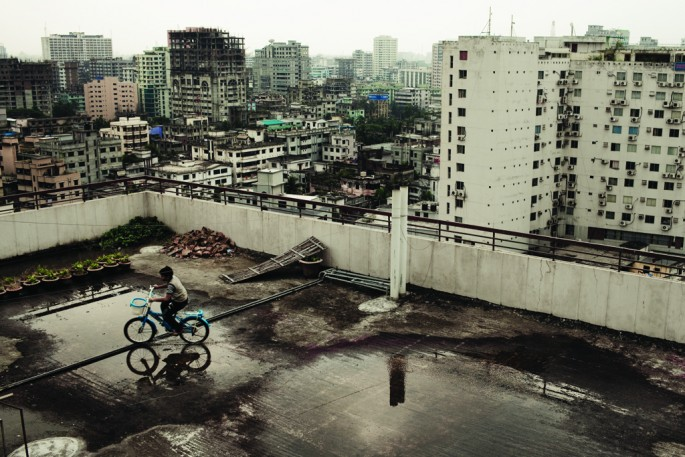 Carlos Cazalis, </span><span><em>A boy cycles on the rooftop of a prominent neighborhood of Dhaka.</em>, </span><span>2009