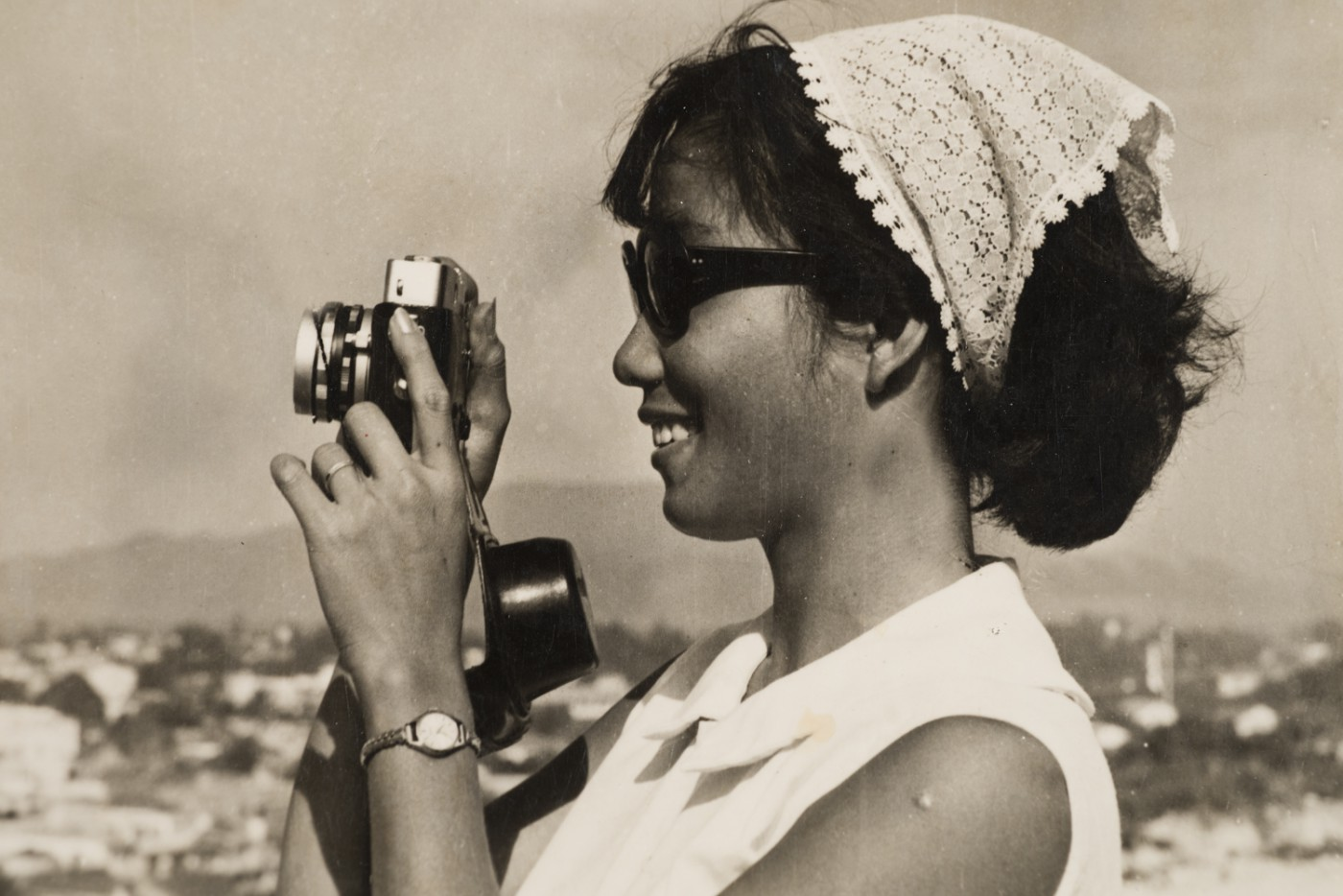Sang Thai, </span><span><em>Luong with a 35mm camera, Nha Trang, Khánh Hòa, Vietnam</em>, </span><span>1962. Gelatin silver print. Courtesy of the Lu-Thai family.
