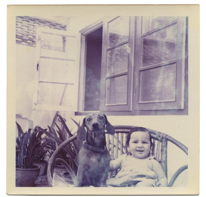"Anil Dewan, </span><span><em>Deepali with her dog on a wicker garden chair, New Delhi, India</em>, </span><span>1972. Dye coupler print, 3.4 x 3.4"". Courtesy of Deepali Dewan."