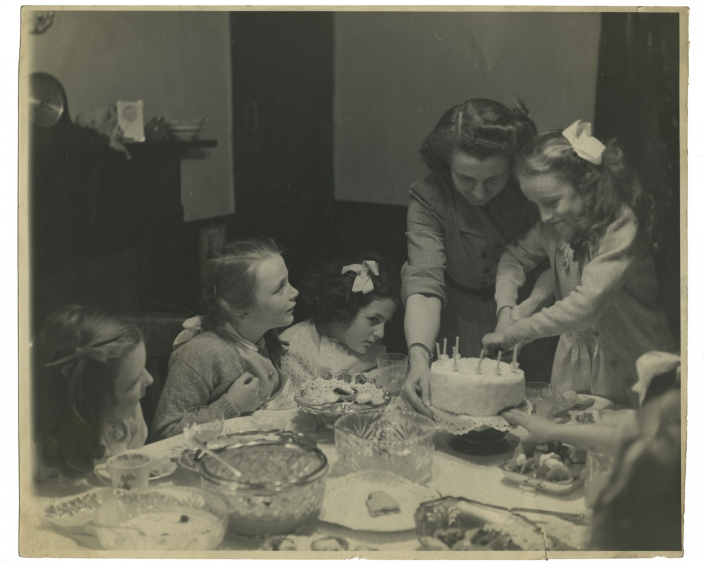"Derry Martin, </span><span><em>Felicity cutting her cake with her mother Kitty and friends on her 8th birthday, England</em>, </span><span>April 1948. Gelatin silver print, 7.5 x 9.25"". Courtesy of Somerset Family."
